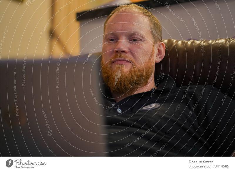 """""""Moskau / Russland - Dezember 2019: Volvo-Mitarbeiter sitzt zu Hause auf der Couch und arbeitet am Computer und arbeitet von zu Hause aus mit einem Coronavirus""""."""