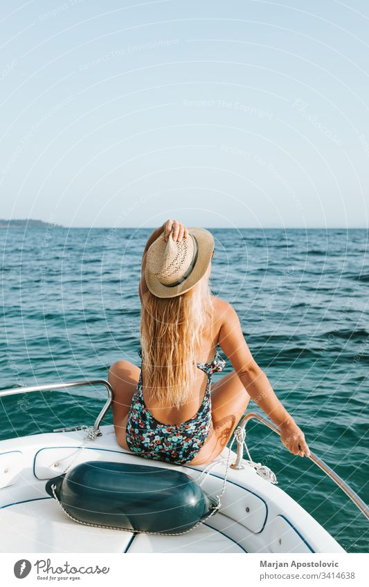 Junge Frau genießt auf dem Deck eines Bootes auf dem Meer Abenteuer attraktiv schön Schönheit blau Kaukasier Kreuzfahrt Schiffsdeck genießen Genuss Mode Spaß