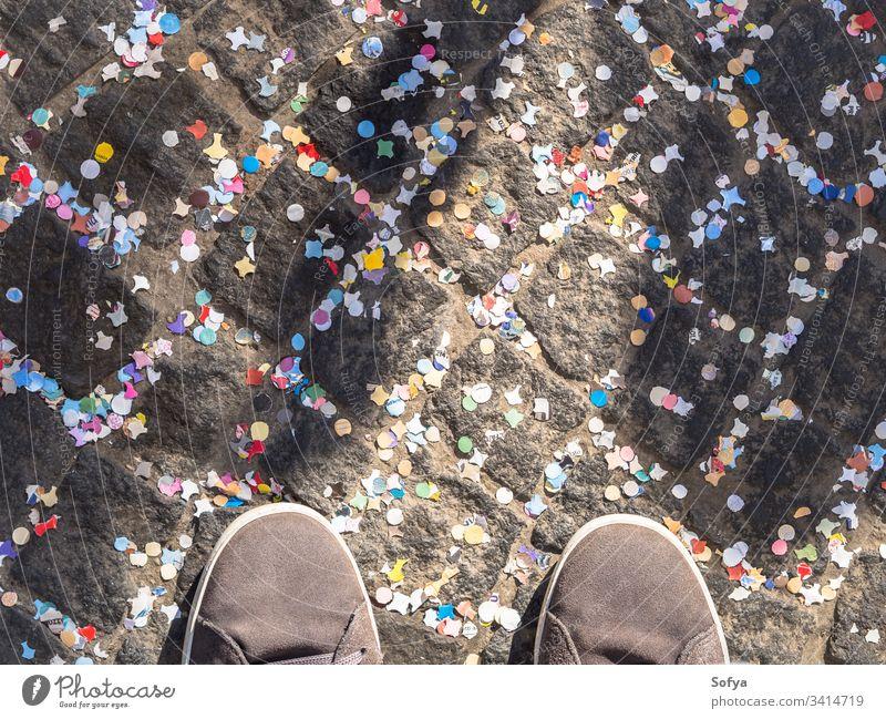 Pflaster mit buntem Konfetti und Schuhen bedeckt Karneval feiern Straße Textur abstrakt Feiertag Farbe Straßenbelag Straßenfotografie urban Detailaufnahme oben