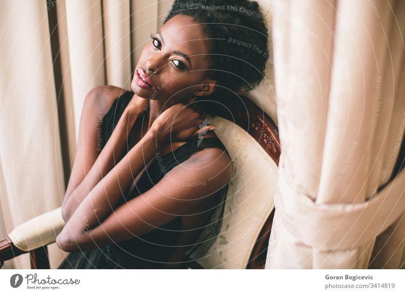 Junge schwarze Frau im Raum Afro-Look Ethnizität Windstille Erwachsener sitzen Mädchen heimwärts Amerikaner charmant Stuhl Freizeit attraktiv Gelassenheit