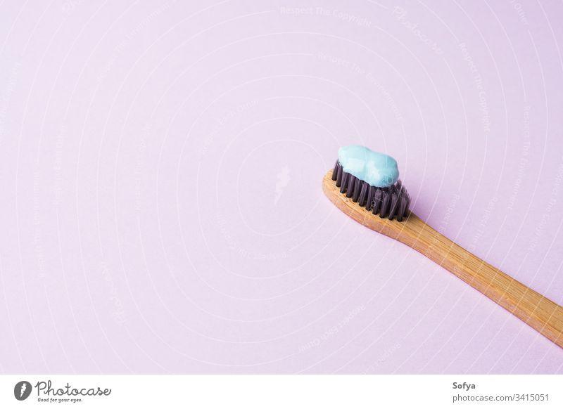 Bambus-Zahnbürste auf rosa Pastell-Hintergrund Hygiene dental Zahncreme blau Personal Fliederbusch Konzept Frühling Zähne trendy mündlich modern sehr wenige