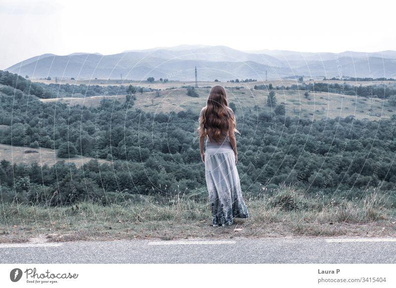 Einsame Frau mit langen Haaren, die auf einen Hügel schaut sorgenfrei glauben Sprit Gedanken Wind Behaarung träumen Tag Hintergrund Gras Erwachsener Blick