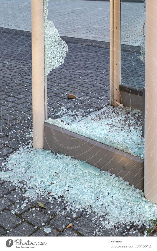 Scherben an einer zerschlagenden Telefonzelle Glasscherben Aggression Tatort Kriminalität Gewalt Politik Textfreiraum unten Pflastersteine Zerstörung Stein