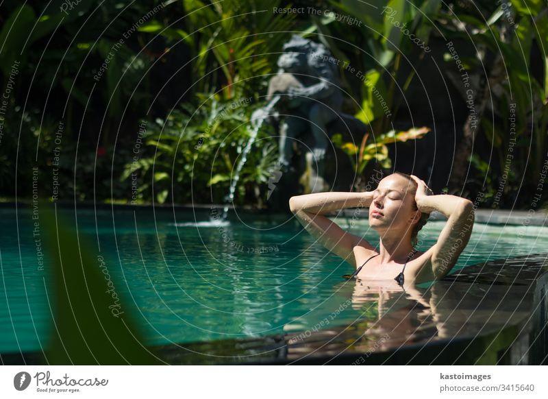 Sinnliche junge Frau entspannt sich im Infinity-Spa-Pool im Freien, umgeben von üppigem tropischem Grün in Ubud, Bali. Wellness Wasser Natur Schwimmsport