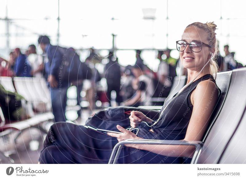 Eine weibliche Reisende, die ihr Handy benutzt, während sie an den Abfluggates des asiatischen Flughafenterminals auf das Einsteigen in ein Flugzeug wartet.