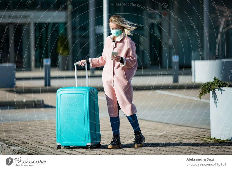 Frau mit Schutzmaske steht am Flughafen-Eingang mit Smartphone und großem Gepäckkoffer, blättert, simst, benutzt mobile Apps. Sicheres Reisen. Ankunft plaudernd