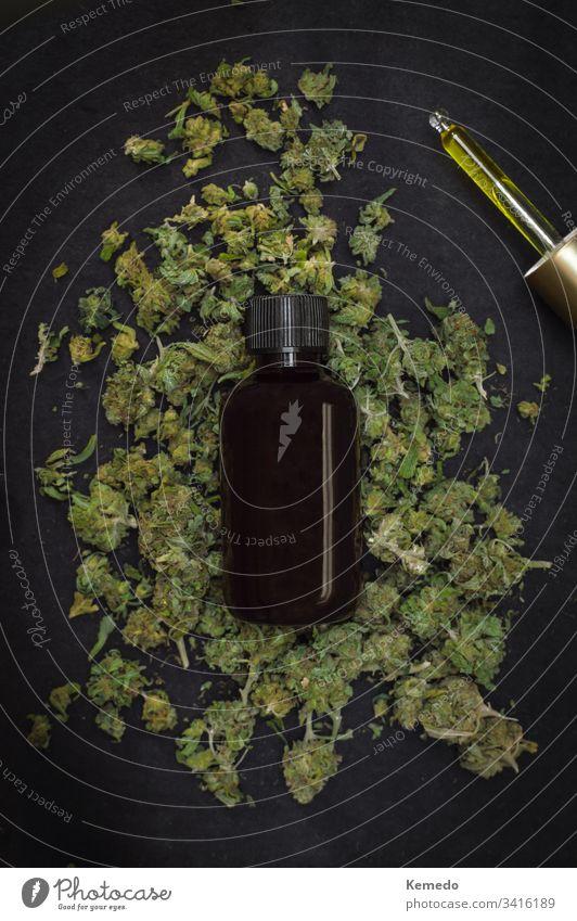 Berg von Marihuana-Knospen mit einer Flasche CBD-Make mit Cannabis oben isoliert auf schwarzem Hintergrund. CBD oder Cannabidiolprodukt. cbd Erdöl Unkraut