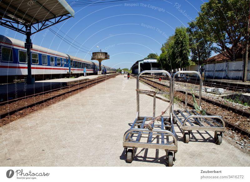 Bahnsteig, Gepäckwagen und Zug nebst Wasserturm im Bahnhof von Phan Thiet, Vietnam Eisenbahn Schönes Wetter Himmel blau Verkehr Gleise Ferien & Urlaub & Reisen