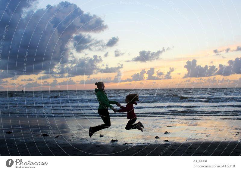 Zwei Mädchen machen einen Luftsprung am Meer im Sonnenuntergang Kontrast Silhouette Kind Kindheit Strand Wolken Sprung springen Spaß Freiheit Freude