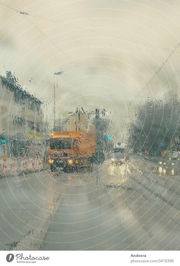 Straße mit Autos im Regenwetter nass Himmel Regenhimmel Scheinwerfer Licht Laterne Haus Reflexion Lampe PKW Stadt Verkehr Spiegelung Schienen Oberleitung dunkel