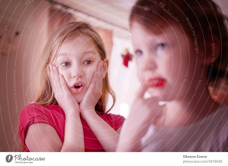 Die ältere Schwester ist überrascht, dass die jüngere ihre Lippen mit rotem Lippenstift bemalt hat Familie schön niedlich Kaukasier wenig Zusammensein Liebe