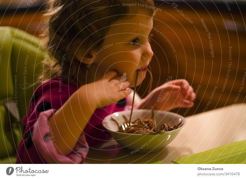 Das gelockte kleine Mädchen mit Appetit isst Buchweizennudeln, Spaghetti. Das Konzept des guten Appetits, leckeres selbstgemachtes Essen. bezaubernd