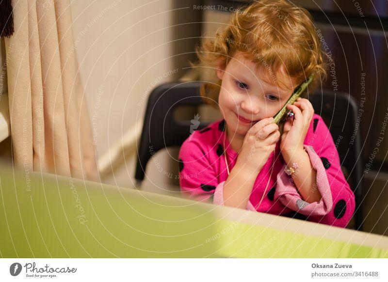 Das gelockte kleine Mädchen spricht mit seiner Großmutter am Telefon. Sie lächelt, erzählt den Nachrichten, wie es ihr geht. bezaubernd attraktiv Baby schön