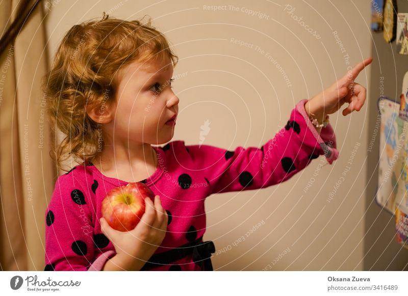 Mädchen, das einen Apfel isst und etwas zeigt schön Business Lebensmittel Vegetarier menschlich Essen leer natürlich Präsentation Kaukasier Ausdruck Porträt