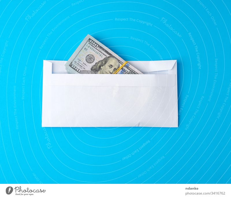 Packung Papier Amerikanische Hundert-Dollar-Scheine, die mit einem Gummiband gebunden sind und in einem weißen Umschlag liegen Geld Kuvert Business Finanzen