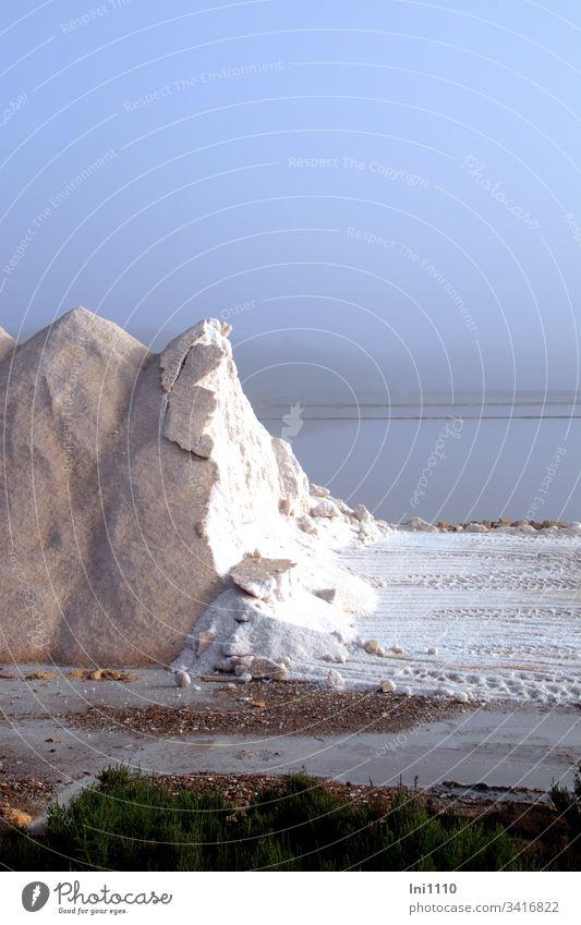 abgetragener Salzberg mit Einblick auf das weiße Salz im Hintergrund die Saline im bläulichem Morgennebel Salzgewinnung Mittelmeer altes Handwerk Industriezweig