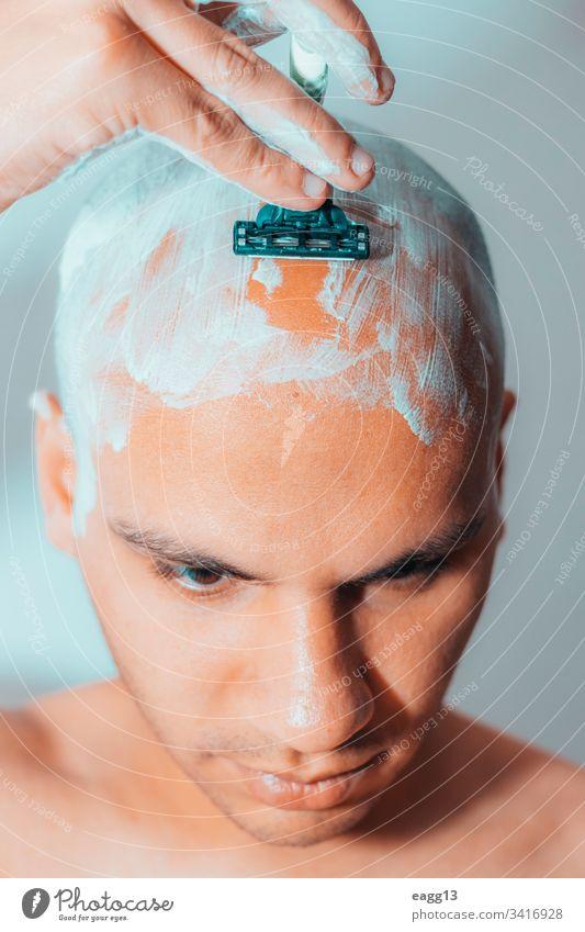 Mann rasiert seinen Kopf mit weißem Schaumstoff Vorschein kahl kahl werdend Bad Klinge Pflege Konzentration abgeschnitten Enthaarung Tatkraft Ausdrücken Auge