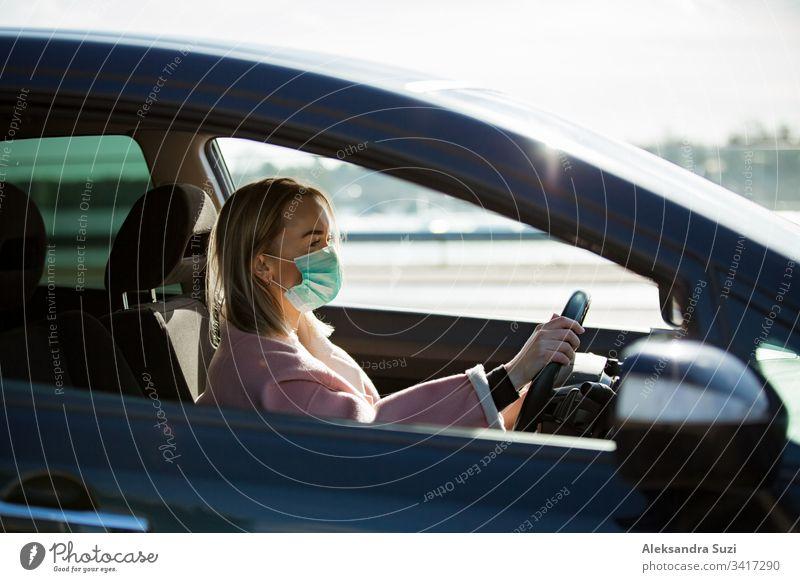 Frau mit Schutzmaske, die ein Auto auf der Straße fährt. Sicheres Reisen. Automobil Atmung PKW Großstadt Coronavirus covid-19 Armaturenbrett Ausflugsziel