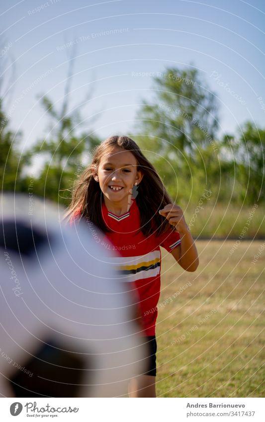 Kleines Mädchen spielt Kind wenig Fußball Jugend Lächeln außerhalb Ball jung Gras Kinder Hände auf den Hüften vertikal im Freien Selektiver Fokus Uniform grün