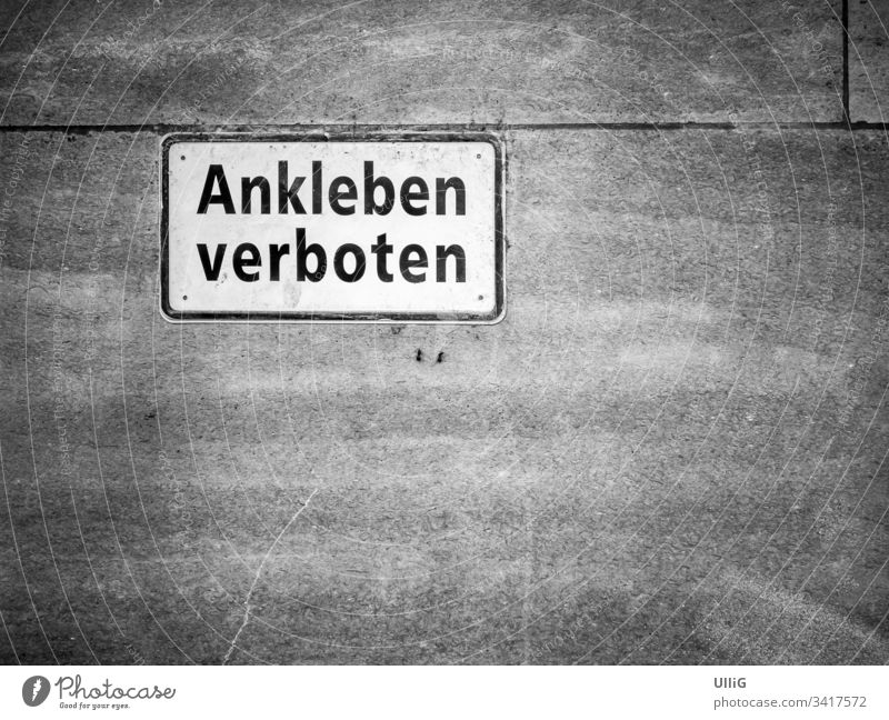 """Ankleben verboten - Verbotsschild mit der Aufschrift """"Ankleben verboten"""", dass lustigerweise an eine Steinmauer geklebt wurde, mit viel Copyspace. ankleben"""