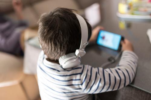 Junge zu Hause, der mit Kopfhörern auf das Telefon schaut Kind Smartphone Technik & Technologie Sucht unsachgemäß 3-4 Jahre alt 4-5 Jahre alt heimwärts
