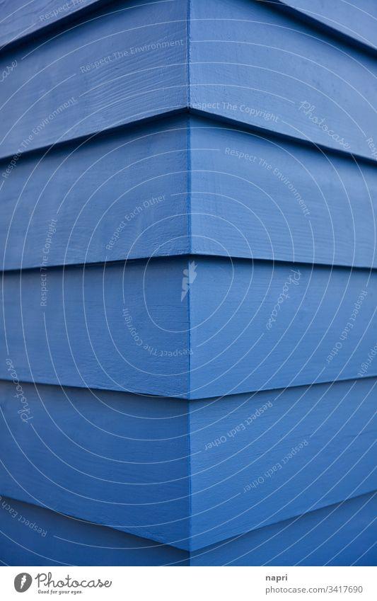 Ecke eines Gebäudes dessen Fassade mit blau gestrichenen Holzbrettern verkleidet ist. Blau Abstrakt Architektur Kante Linien geometrisch Hintergrund Haus Muster