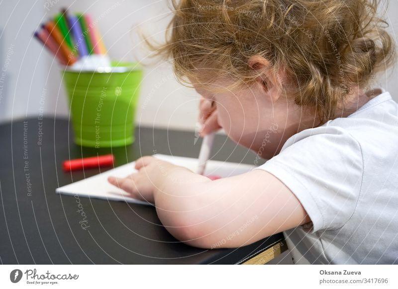 Ein Mädchen ist Wittling. Schreibwaren bunte Schreibgeräte, Zubehör, Filzstifte, farbiges Papier, Bücher. Hausunterricht Coronavirus Heimunterricht