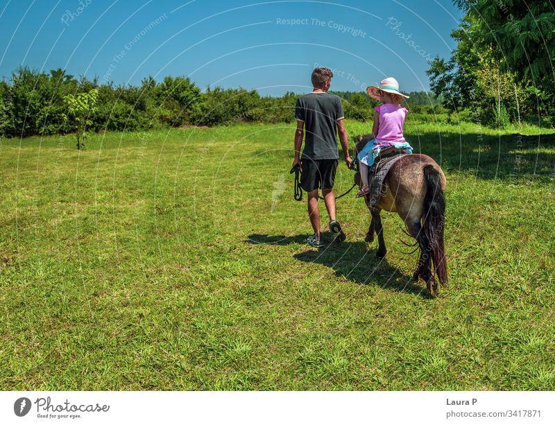 Kleines Mädchen reitet im Sommer auf einem Pony auf einer grünen Wiese Aktivität Tier auf dem Land auf dem Bauernhof schön züchten Pflege Kind Kindheit