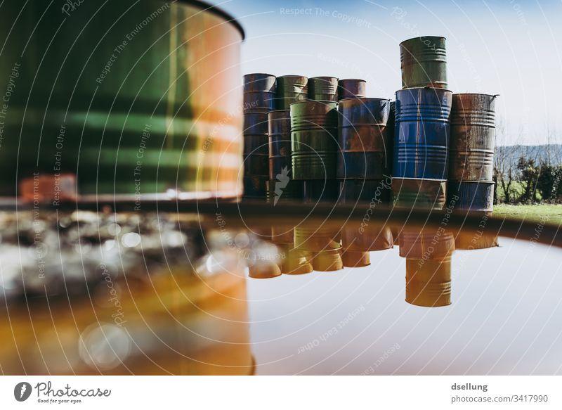 Aufgestapelte, rostige Metallfässer spiegeln sich in Pfütze bedrohlich Umweltschaden Teile u. Stücke trocken Hintergrundbild Umweltschutz Schaden Riss bizarr