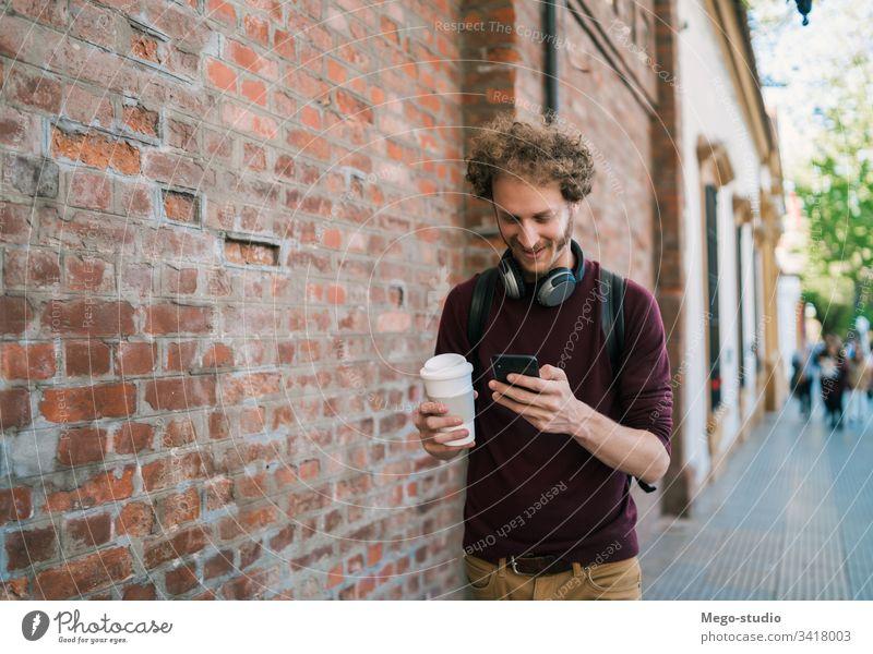 Junger Mann benutzt sein Mobiltelefon. Mobile Telefon Person Erwachsener männlich jung Menschen außerhalb gutaussehend Glück Zelle attraktiv
