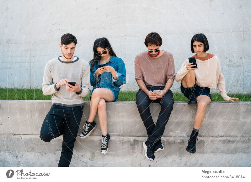 Gruppe von Freunden, die ihr Telefon benutzen. Handy Freundschaft Menschen jung vier Personen Drahtlos Gerät Zusammengehörigkeitsgefühl modern Touchscreen