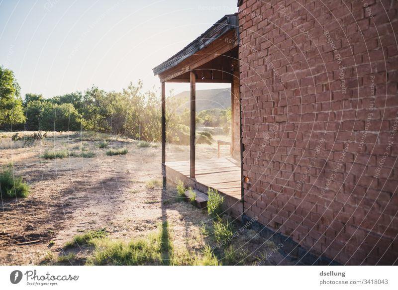 Backsteinhaus mit hölzernem Vordach im Gegenlicht historisch Altstadt Fassade Bauwerk Gebäude Ruhe Einsam verlassen Architektur Abenteuer um die ecke