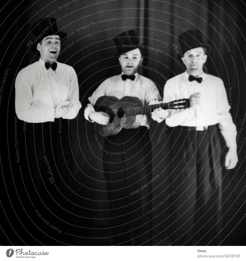 unplugged portrait ganzkörper historisch damals nostalgie festlich stehen halten Gitarre zylinder fliege hemd hose outfit vortrag musik konzert drei vorhang