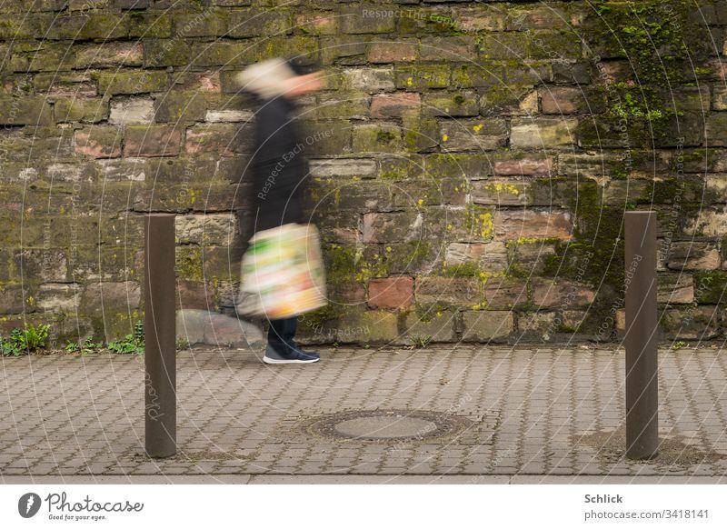 Mensch oder Außerirdischer mit bunter Plastiktüte geht vor schmutziger Wand Bewegungsunschärfe gehen Mann Pfosten Langzeitbelichtung Gully Gullydeckel