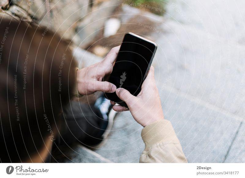 Rückansicht eines jungen Mannes, der im Freien sitzend ein Mobiltelefon benutzt männlich Sitzen 1 Telefon Mobile Beteiligung Menschen photogen modern Typ Person