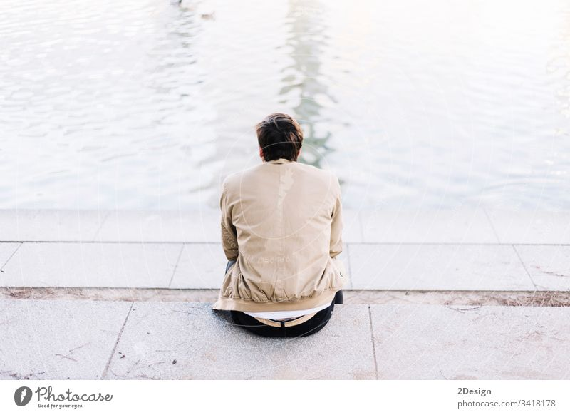 Hübscher junger Mann auf dem See an einem sonnigen, friedlichen Tag 1 Person Erholung Himmel Rücken Freizeitkleidung attraktiv Sitzen photogen männlich trendy