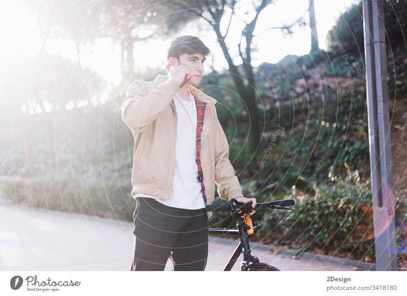 Junger hispanischer Mann, der ein Handy benutzt und ein Fahrrad mit sich führt, wenn er im Freien geht Beteiligung jung 1 Glück Gesicht Person männlich cool