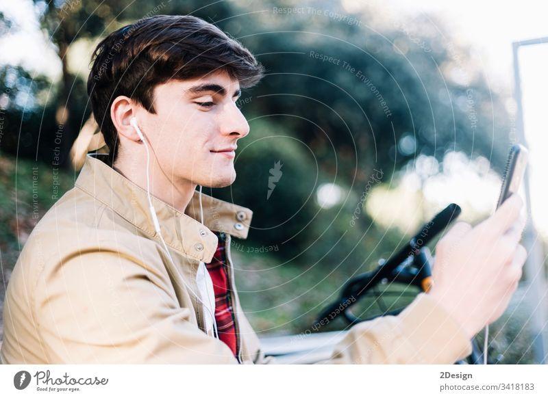 Junger hispanischer Mann, der im Freien sitzend ein Mobiltelefon benutzt männlich Sitzen jung 1 Telefon Mobile Beteiligung Menschen photogen modern Typ Person