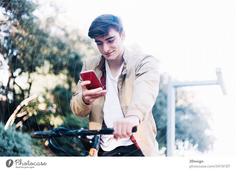 Junger, gutaussehender Typ auf dem Fahrrad, der auf ein Mobiltelefon schaut. 1 Telefon Lifestyle Technik & Technologie Mobile Stil Großstadt Mann jung Rad