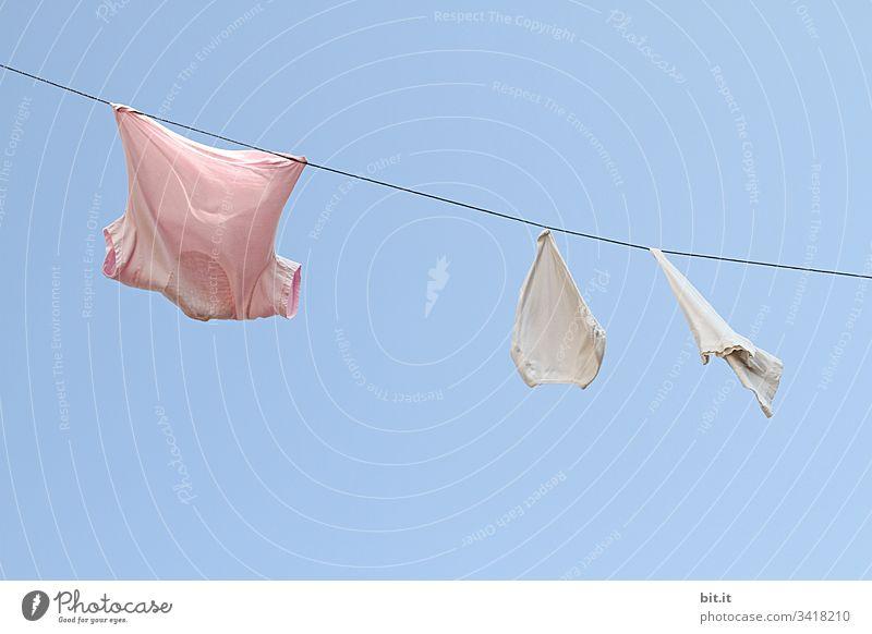 Das frisch gewaschene rosa T-Shirt zeigt der weissen Unterhose dem alten Waschlappen, vor blauem Himmel, wie man nass und duftend am Seil der Wäscheleine bei schönem Wetter zum Trocknen hängt.