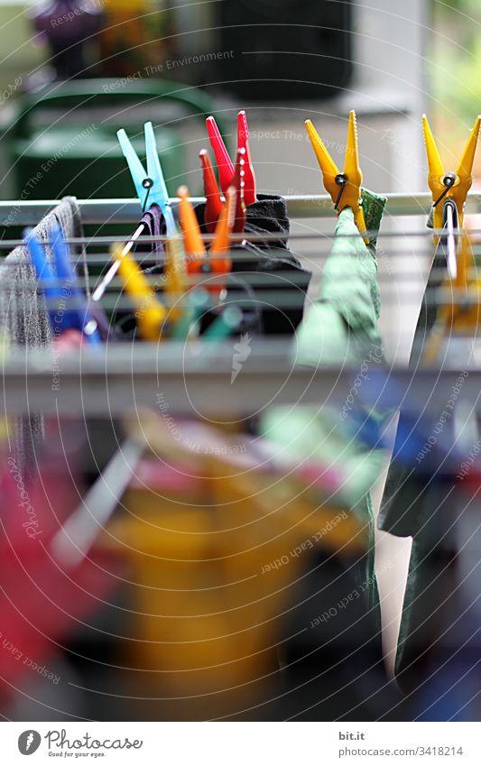 Bunte Wäscheklammern machen den Haushalt und hängen frisch gewaschene Wäsche zum Trocknen auf einen Wäscheständer im Freien, mit geringer Tiefenschärfe.