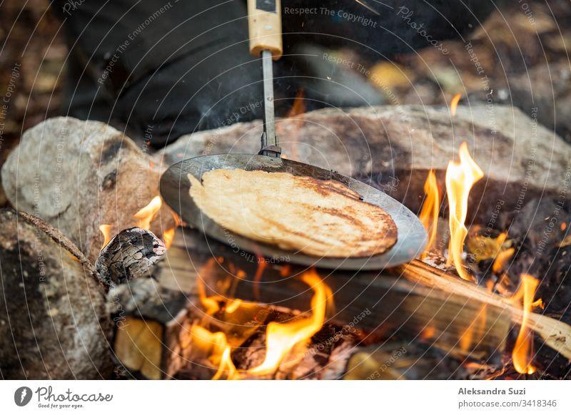 Mann und Frau machen Pfannkuchen am Lagerfeuer im Wald am Ufer des Sees, machen ein Feuer, grillen. Ein glückliches Paar erkundet Finnland. Skandinavische Landschaft.