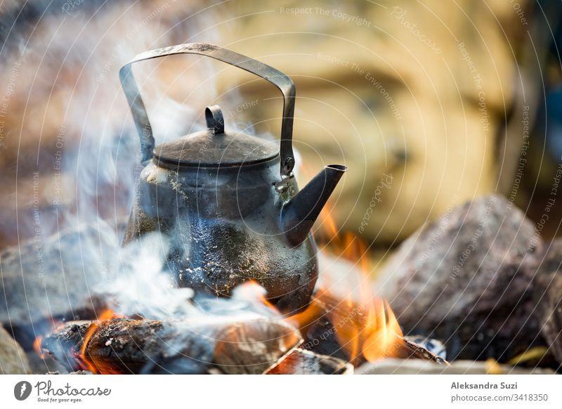 Mann und Frau machen Kaffee in einem großen Kessel am Lagerfeuer im Wald am Seeufer, machen ein Feuer, grillen. Ein glückliches Paar erkundet Finnland. Skandinavische Landschaft.