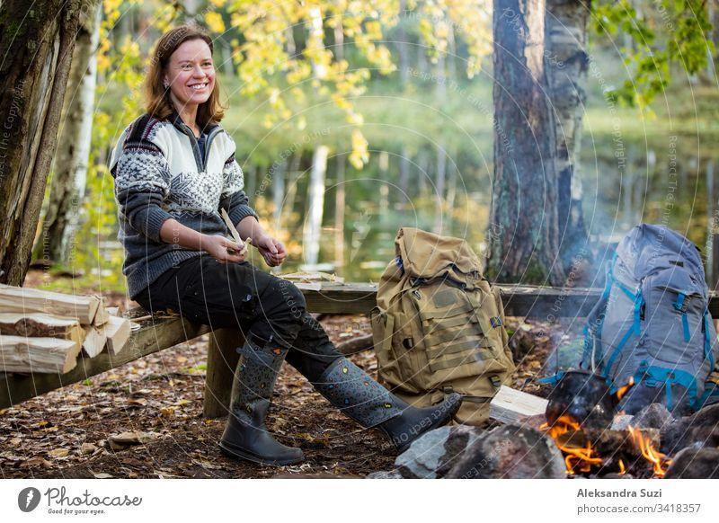 Mann und Frau rösten am Lagerfeuer im Wald am Ufer des Sees, machen ein Feuer, grillen. Ein glückliches Paar erkundet Finnland. Skandinavische Landschaft. aktiv