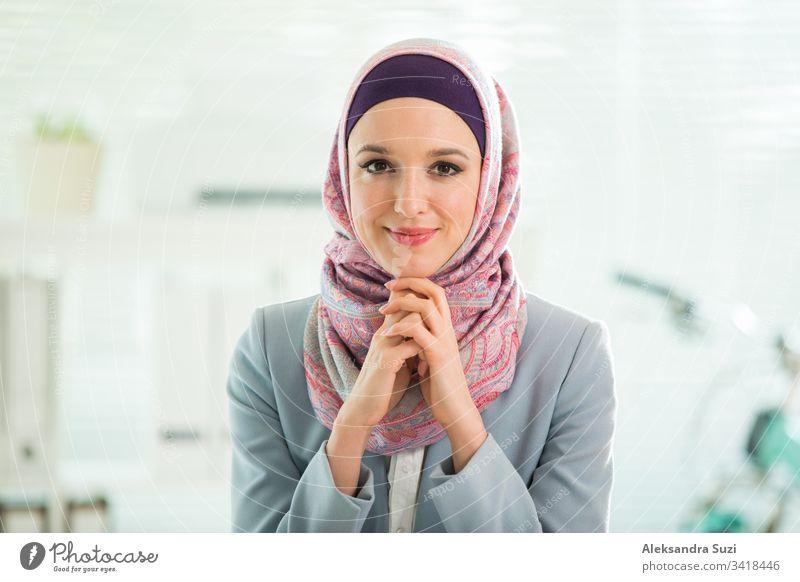 Schöne, stilvolle Frau mit Hijab und Brille, die im Büro am Schreibtisch mit Laptop sitzt. Porträt einer selbstbewussten muslimischen Geschäftsfrau. Modernes Büro mit großem Fenster, Fahrrad im Hintergrund.