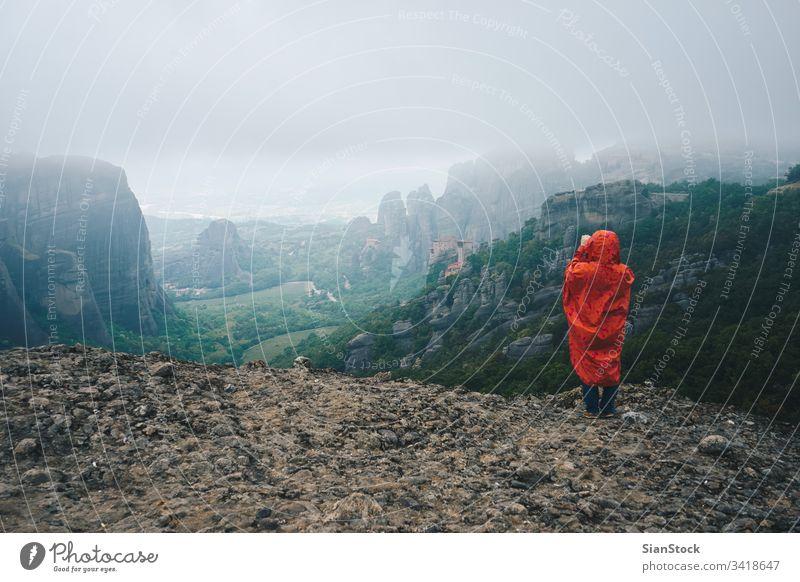 Frau mit rotem Regenmantel fotografiert mit ihrem Smartphone die Landschaft der Meteora-Felsen, Griechenland Kloster Nebel Berge u. Gebirge wandern Tour