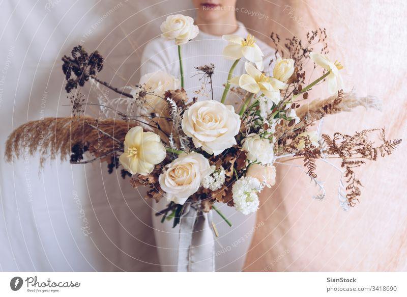 Junge Frau in einem weißen Kleid mit einem Blumenstrauß in der Hand. Vintage, romantisches Konzept. Mädchen weiches Licht schön altehrwürdig Hochzeit jung