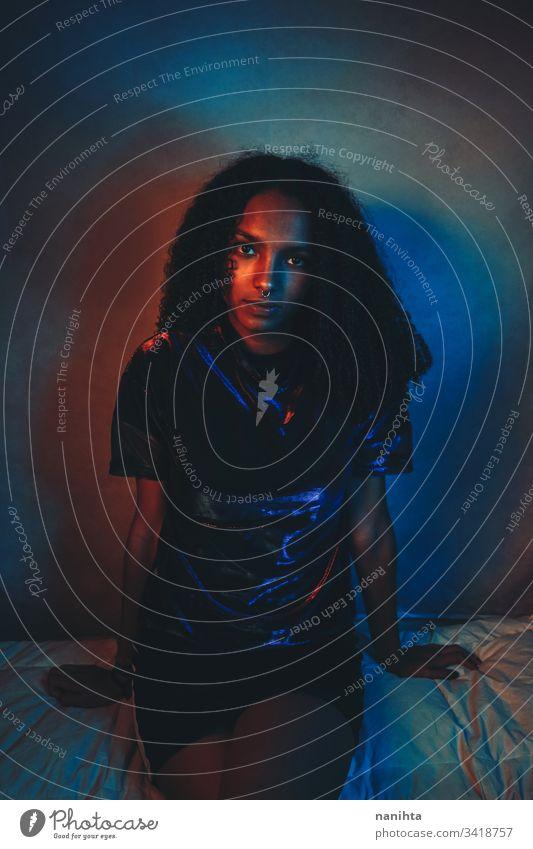 Künstlerisches Porträt mit Farblicht einer jungen Frau neonfarbig schwarz Kunst künstlerisch cool Afro-Look Afroamerikaner Afrikanisch Jugend frisch Nacht blau