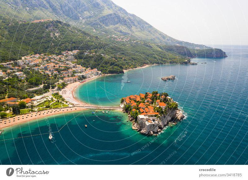 Kleine private Halbinsel an der Küste Montenegros Sveti Stefan Meer Urlaubsstimmung reisen Sightseeing Badeort Strand Felsen Segelboot Berge u. Gebirge Hotel