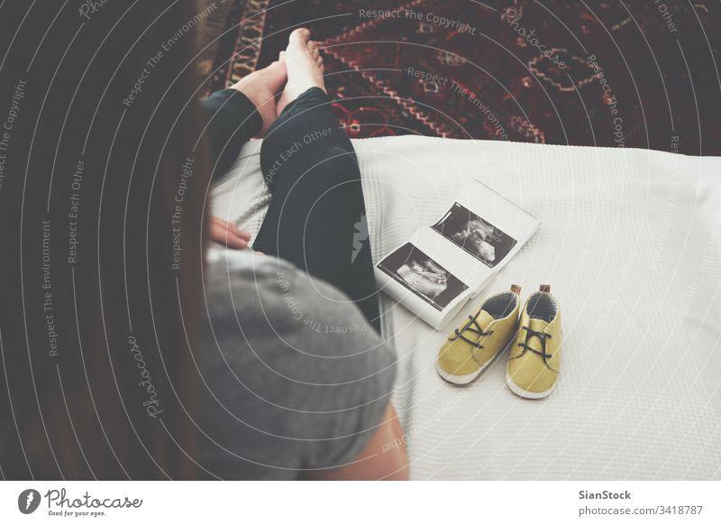 Junge schwangere Frau entspannt sich auf dem Sofa Schwangerschaft Baby Bauch heimwärts Ultraschall-Scan Mutterschaft erwartend Glück Top Ansicht Schuhe gelb